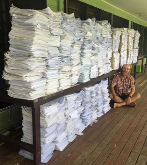 Vyplněné dotazníky čekají na zanesení do databáze, v pozadí Vojtěch Novotný, seniorní autor studie.